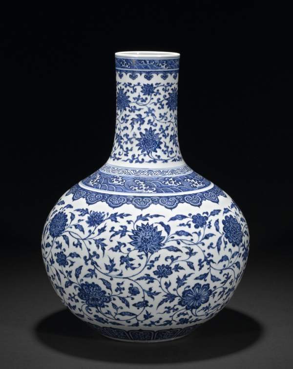 A blue and white porcelain vase, tianqiuping, Yongzheng (1722–35) mark and period, with interlocking lotus, pomegranate, peony, camellia and seasonal flowers and bands of waves.