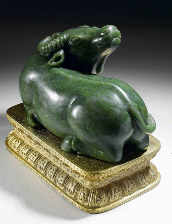 a Chinese Imperial spinach-green jade water buffalo, with a gilt bronze stand, Qing Dynasty, Qianlong period (1736–95), 20.8 cm.;